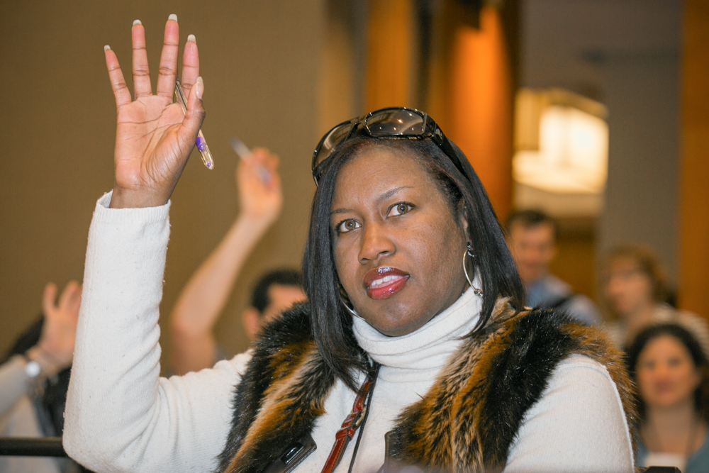 A teacher raises her hand with a question at the NASTA Forum