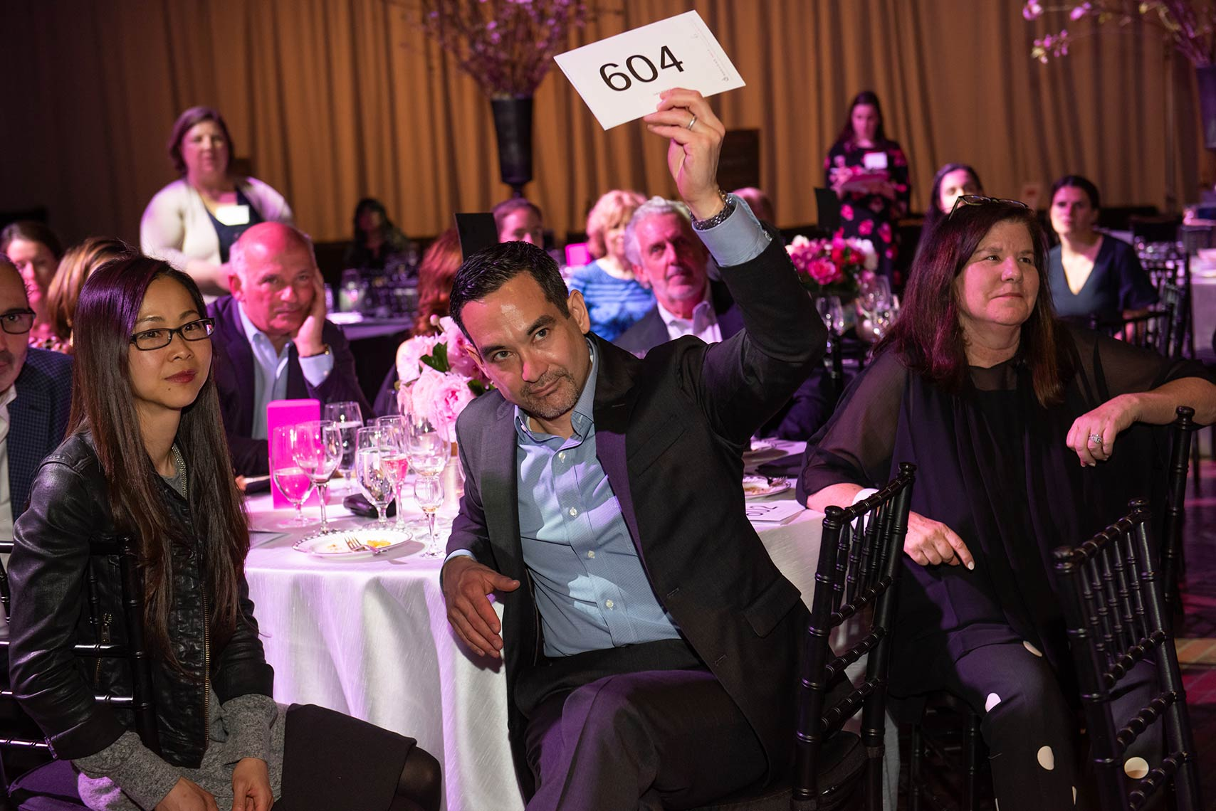 Gala attendee holds his bid number for the charity auction for Rosie