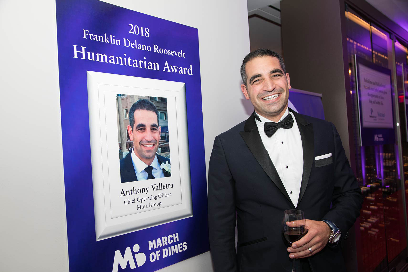 010-Humanitarian-Award-recipient-Anthony-Valletta-stands-next-to-his-promotional-sign-at-the-Black-Ties-for-Babies-gala