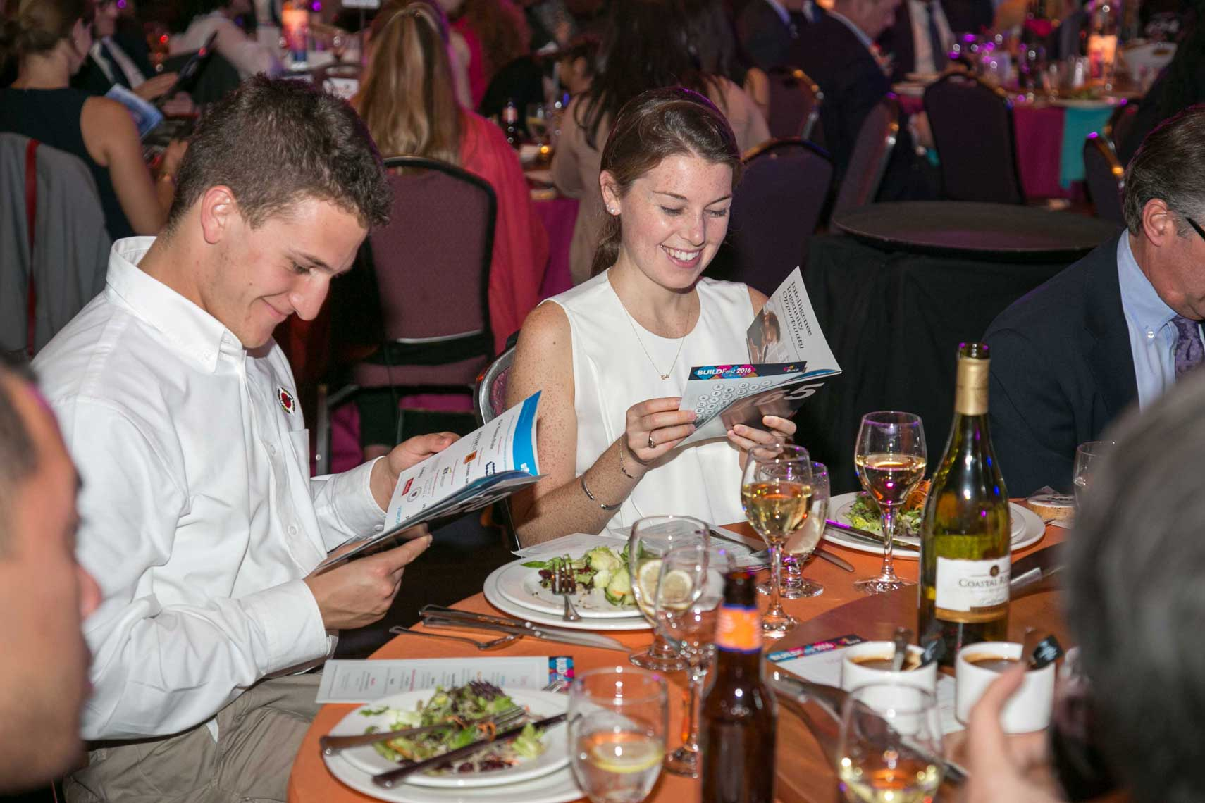 Guests Look Over the Program at BuidFest Boston Gala 2016
