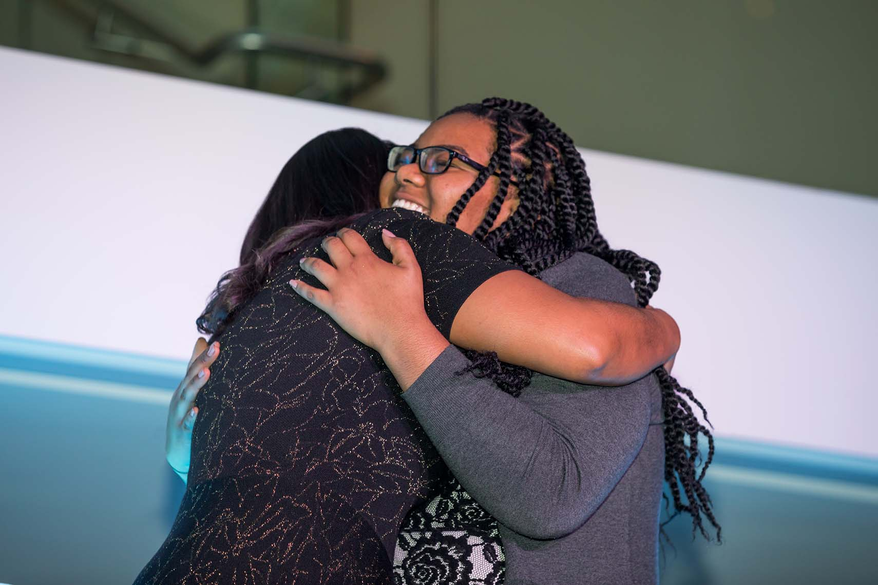Big and Little Sisters embrace after speaking on stage
