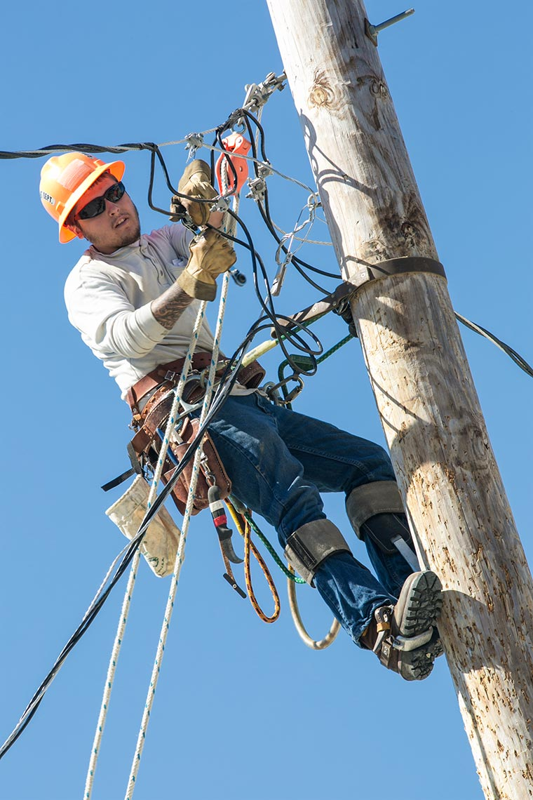 NEPPA Lineman on Pole Clamps Down on Wire at Rodeo Day