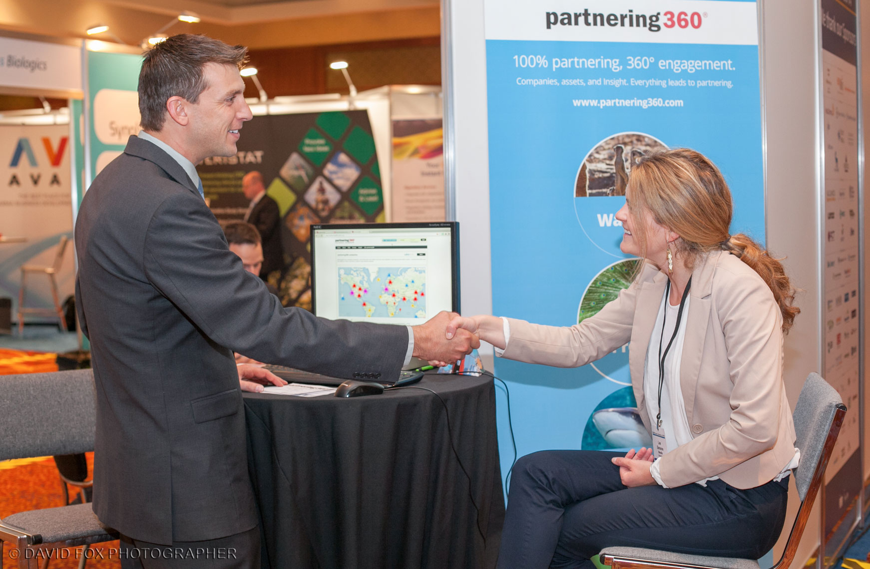 Trade Show Vendor and Attendee Shake Hands at Meeting