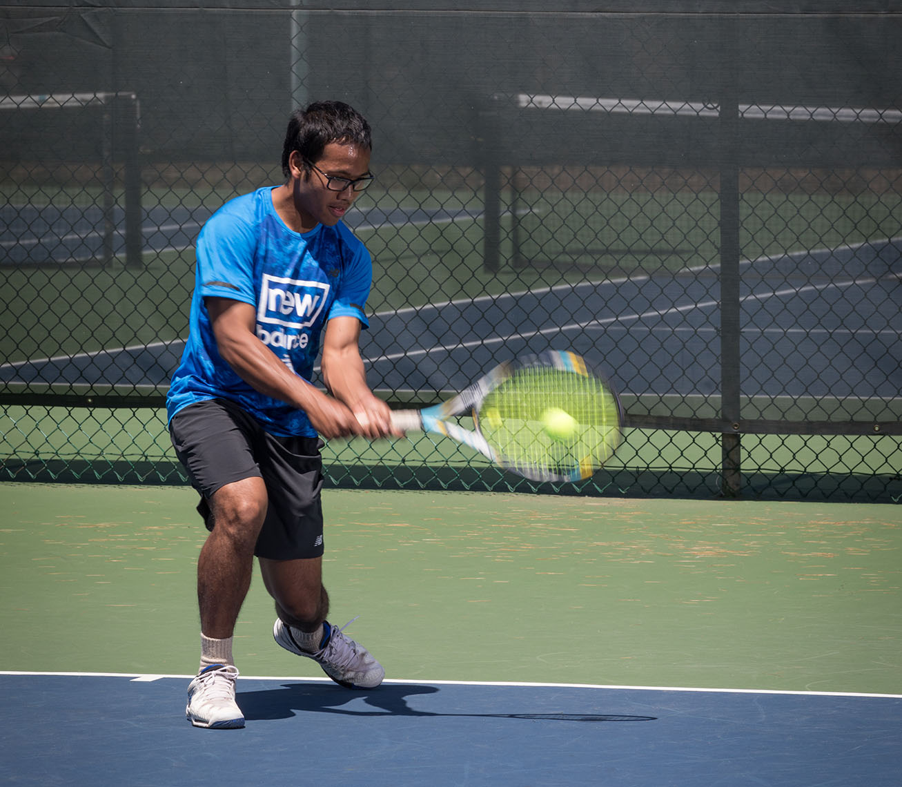 Young man strikes tennis ball on court with USTA New England