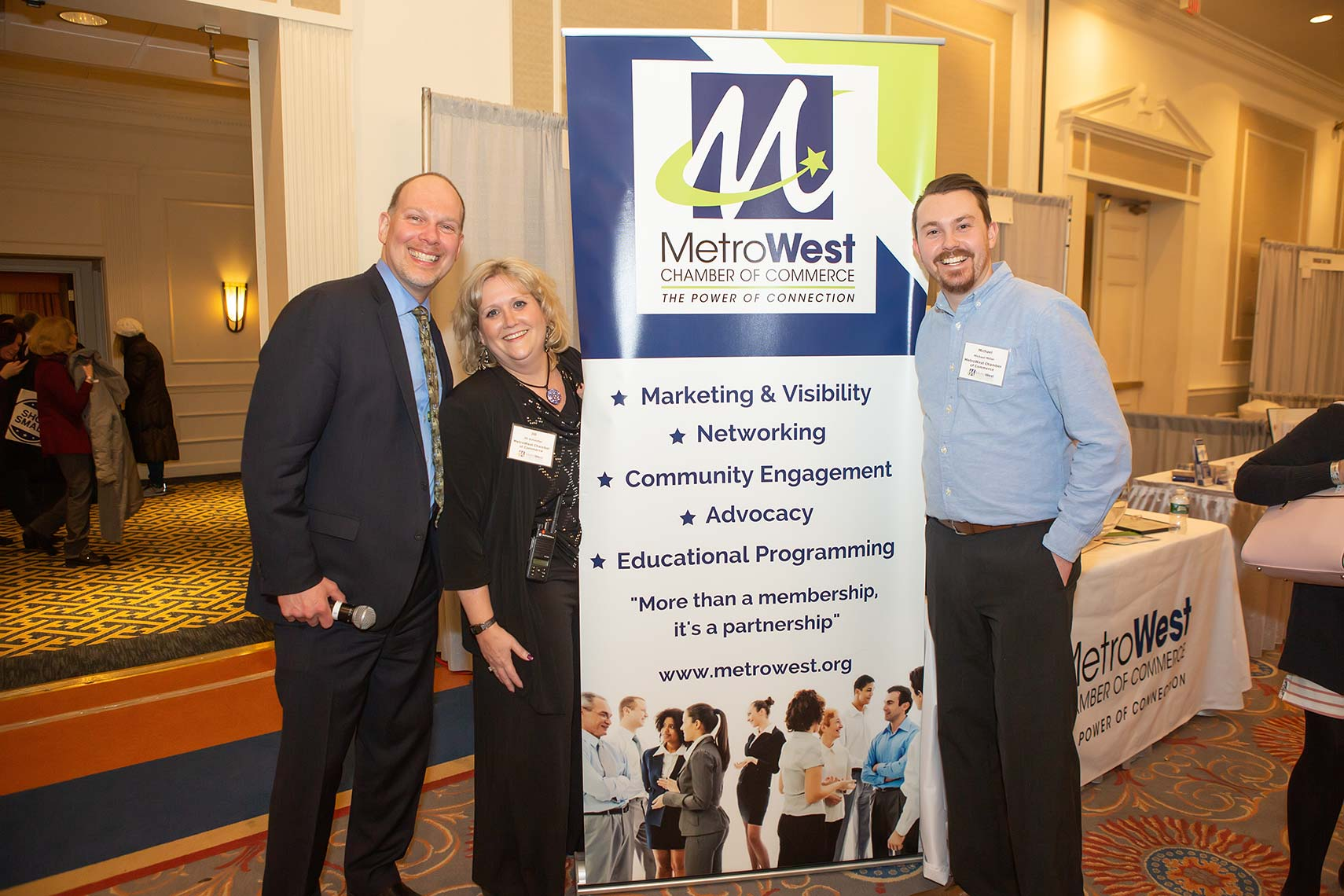 Metrowest Chamber of Commerce members pose by sign at Taste of Metrowest