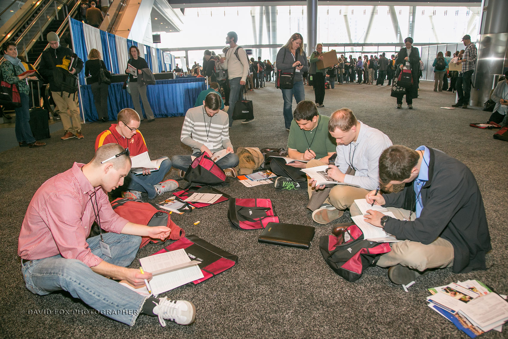 Conference Attendees Sit on Floor and Go Over NASTA Material