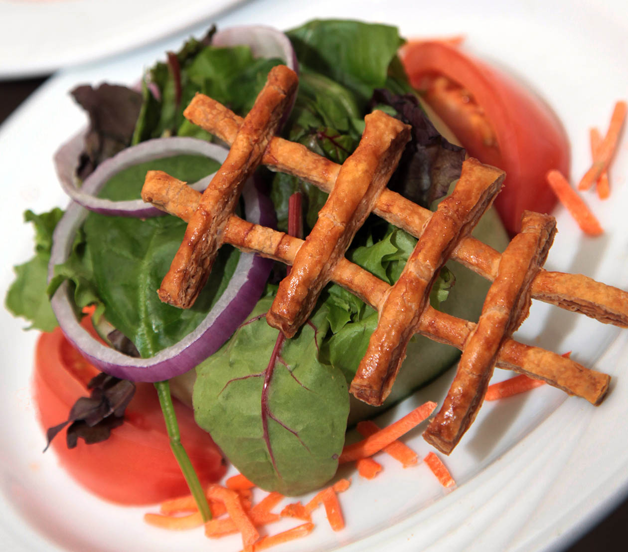 Salad on a Plate topped with a Pretzel
