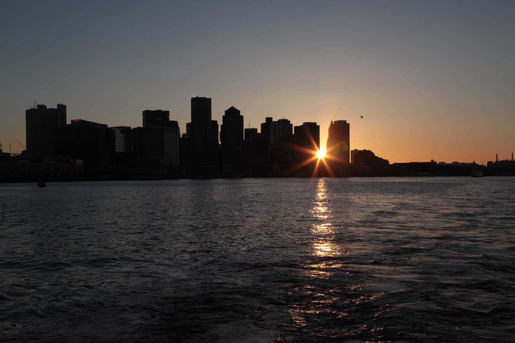 Sunburst over the Boston skyline from the harbor
